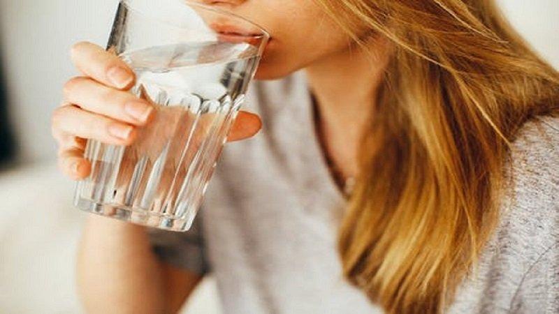 A model enjoying her glass of water